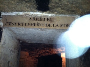 """Paris catacombs with sign, """"Stop! Here is the empire of death."""" / Photo by Ilana DeBare"""