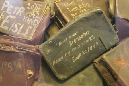 Suitcases with names and home addresses in Auschwitz display case / Photo by Ilana DeBare